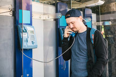 Young attractive modern man talking on the payphone Royalty Free Stock Images