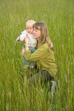 Young attractive mom with  little baby. In the meadow Stock Image