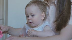 Young attractive mother with cute little daughter. Mom and baby girl doing models by plasticine. A young attractive mother with her young child makes different stock footage