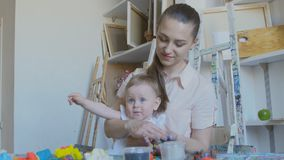 A young attractive mother with her little child mixes different colors of plasticine. Preschool Development. Young attractive mother with cute little daughter stock video footage