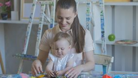 Young attractive nanny is playing with baby in plasticine. Preschool Development. Young attractive mother with cute little daughter. Mom and baby girl doing stock video