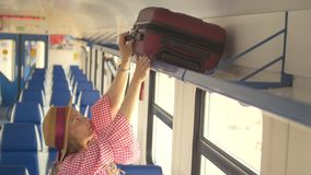 Young attractive mother with daughter going to travel in speed train - puts the suitcase on the top shelf. Close up stock video footage