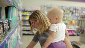 Young attractive mother in glasses holding her child in her arms while choosing diapers on the shelves in the