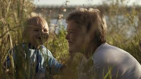 Young attractive mother having fun with her son in beautiful field near the river stock video