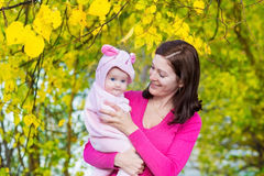 Young attractive mother and her baby in autumn park Stock Images