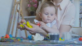 A young attractive mother with her young child makes different figures from soft plasticine. Preschool Development. Young attractive mother with cute little stock footage