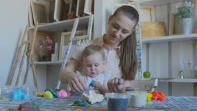 A young attractive mother with her little child mixes different colors of plasticine. Preschool Development. A young attractive mother with her young child stock video footage