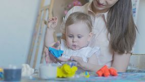 Mother and girl make figures of plasticine and kinetic sand. A young attractive mother with her little child mixes different colors of plasticine. Preschool stock footage