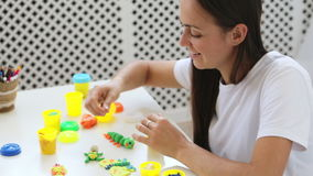 Young attractive mother with little cute daughter play with modeling clay. Young attractive mother with cute little daughter play with modeling clay at light stock footage