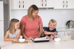 Young attractive mother preparing salad together with little son and young beautiful daughter in healthy vegetable nutrition educa royalty free stock image