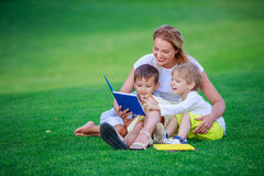 Young attractive mother reads a story book to her two small children Stock Photography