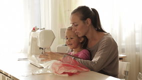 Young attractive mother working on sewing machine with her little cute daughter
