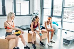 Young attractive multicultural sportswomen sitting on wooden boxes. At gym stock image