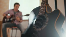 Young attractive musician composes music on the guitar and plays, other musical instrument in the foreground, blurred. Young attractive musician composes music stock video