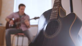 Young attractive musician composes music on the guitar and plays, other musical instrument in the foreground, blurred. Young attractive musician composes music Royalty Free Stock Photography