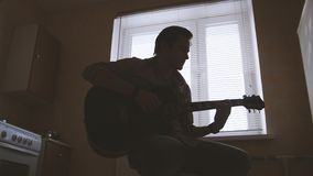 Young attractive musician composes music on the guitar and plays, other musical instrument in the foreground, silhouette. Shot Royalty Free Stock Images