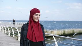 Young attractive muslim girl enjoys having a walk near the sea side with seagulls flying around on the background. Outdoors footage stock video