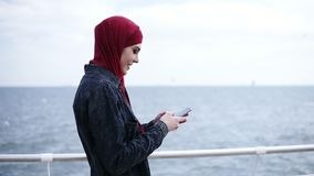Young attractive muslim girl with hijab on her head is scrolling and typing something on her smartphone while walking. Near the sea side stock video