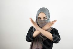 Young attractive Muslim student wearing turban hijab headscarf saying no to war and violence holds her arms crossed. Isolated white background stock photography