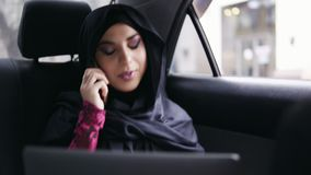 Young attractive muslim woman in hijab sitting on the back seat in taxi and talking on the phone while holding her. Laptop. Slowmotion shot stock video footage