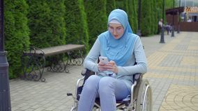 Young attractive muslim woman in a traditional scarf disabled in a wheelchair uses a smartphone sitting in the park stock footage