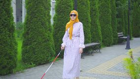 Young attractive muslim woman visually impaired with a walking cane in the park stock video footage