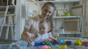 Young attractive mother with cute little daughter. Mom and baby girl doing models by plasticine. Young attractive nanny is playing with baby in plasticine stock video