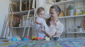 Young attractive nanny is playing with baby in plasticine. Preschool Development. A young attractive mother with her young child makes different figures from stock video footage