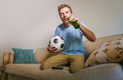 Young attractive and nervous man concentrated watching football game on television holding beer bottle and soccer ball excited in. Stress enjoying the match on Stock Photo