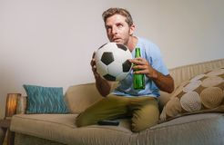 Young attractive and nervous man concentrated watching football game on television holding beer bottle and soccer ball excited in. Stress enjoying the match on Royalty Free Stock Image