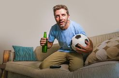 Young attractive and nervous man concentrated watching football game on television holding beer bottle and soccer ball excited in. Stress enjoying the match on Royalty Free Stock Images