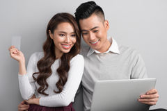 Young attractive and nice happy couple online shopping with cred Stock Image
