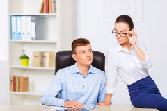 Young attractive office couple at the desk Royalty Free Stock Photography
