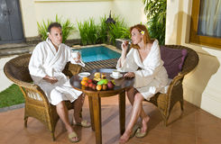 Young attractive pair drinks tea at pool Royalty Free Stock Image