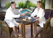 Young attractive pair drinks tea at pool on rest Stock Image