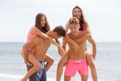 Attractive smiling fellows holds beautiful girls on a seashore on a natural blurred background. Young attractive people on a beach holding appealing girls in Royalty Free Stock Photography