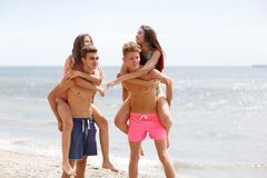 Attractive smiling fellows holds beautiful girls on a seashore on a natural blurred background. Young attractive people on a beach holding appealing girls in Royalty Free Stock Image