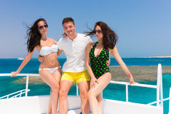 Young attractive people laughing and standing on the yacht at a Stock Images