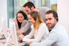 Young attractive people learning their new job at call center Royalty Free Stock Photography