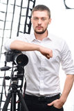 Young attractive photographer leaning on tripod. Professional cameraman. Young male attractive photographer is posing with his tripod and camera stock photo