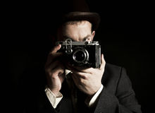 Young and attractive photographer in vintage suit and with retro photo camera. Stock Photo