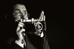 Young and attractive photographer in vintage suit and with retro photo camera. Stock Photos