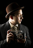 Young and attractive photographer in vintage suit and with retro photo camera. Royalty Free Stock Images