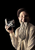 Young and attractive photographer in vintage suit and with retro photo camera. Royalty Free Stock Photo