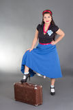 Young attractive pinup girl posing with suitcase Stock Images