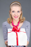 Attractive pinup woman in striped dress giving a present Stock Images