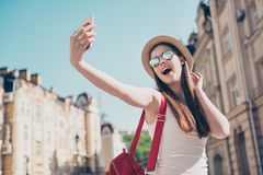 Young attractive playful tourist is making selfie on the phone o Stock Photos