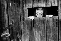 Young positive woman peeking from the crack in the wooden shed. Royalty Free Stock Photo