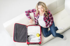 Young attractive pregnant woman packing children's wear Royalty Free Stock Photography