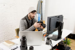 Young attractive press photographer holding photographic camera viewing his work on editor office desk Royalty Free Stock Images